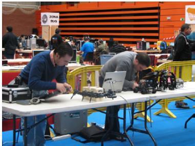 Foto de Ricardo y Alejandro en la mesa con la Granja de  Robots.